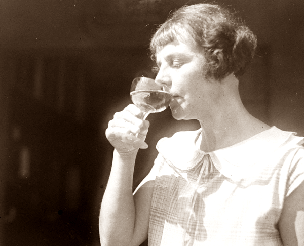 Larger image of woman, c.1930, drinking wine.